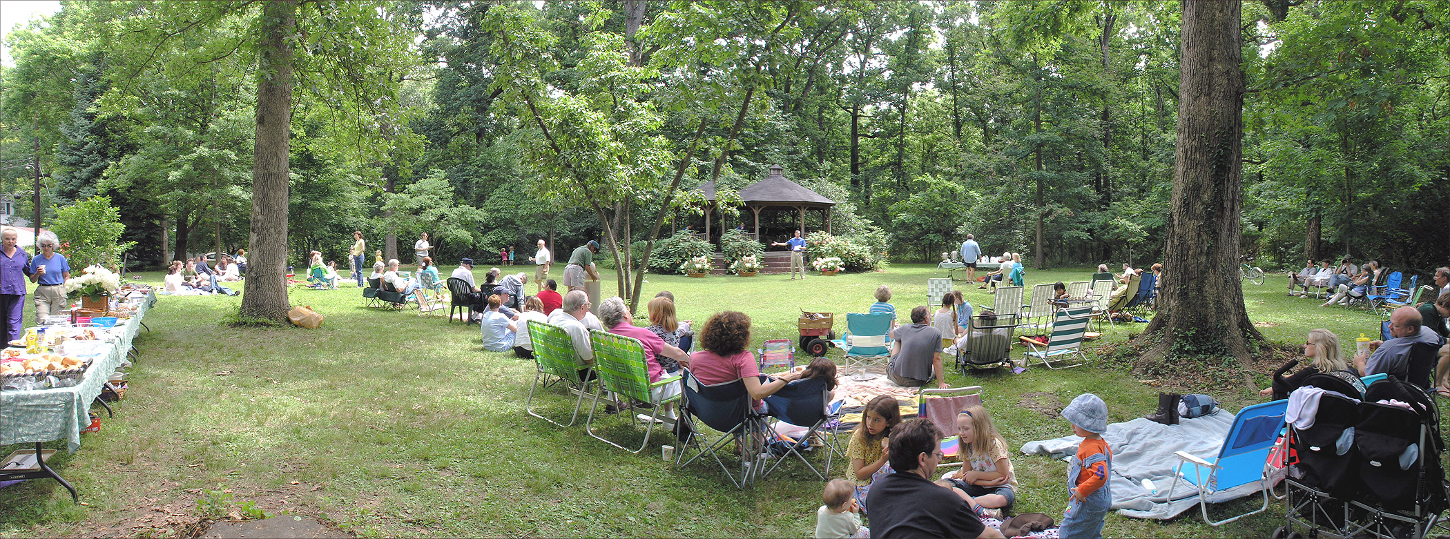 Panorama of people picnicking in front of the gazebo