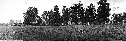 Field with houses in distance